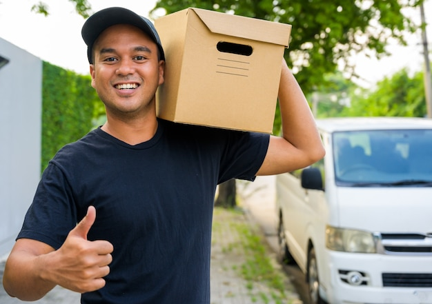 Jeune livreur en uniforme noir montrer la thumbup et tenant une boîte en papier.