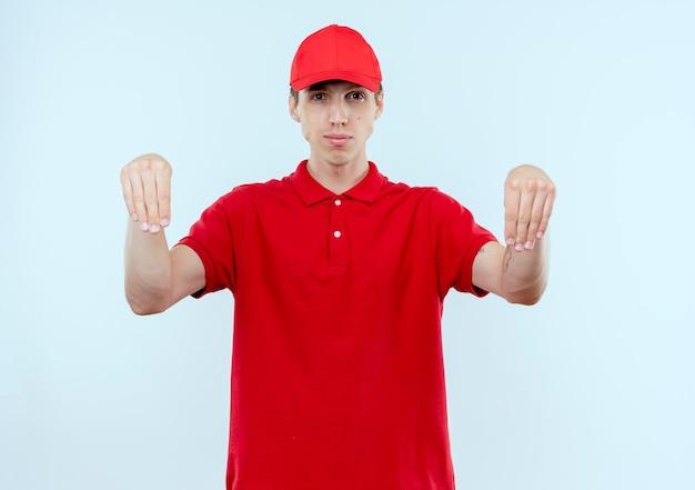 Jeune livreur en uniforme rouge et cap à la confiance en faisant des gestes avec les mains, le concept de langage corporel debout sur un mur blanc