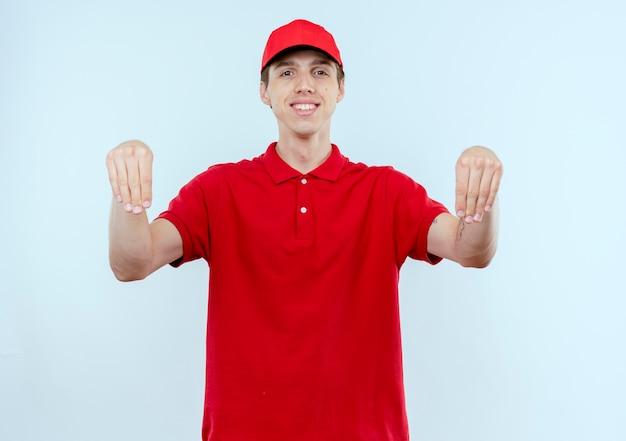 Jeune livreur en uniforme rouge et cap à la confiance souriant gesticulant avec les mains, le concept de langage corporel debout sur un mur blanc