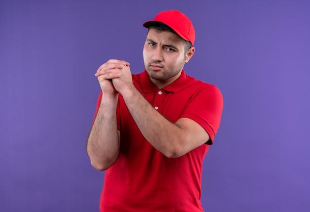Jeune livreur en uniforme rouge et cap faisant le geste de travail d'équipe main dans la main avec un visage sérieux debout sur un mur violet