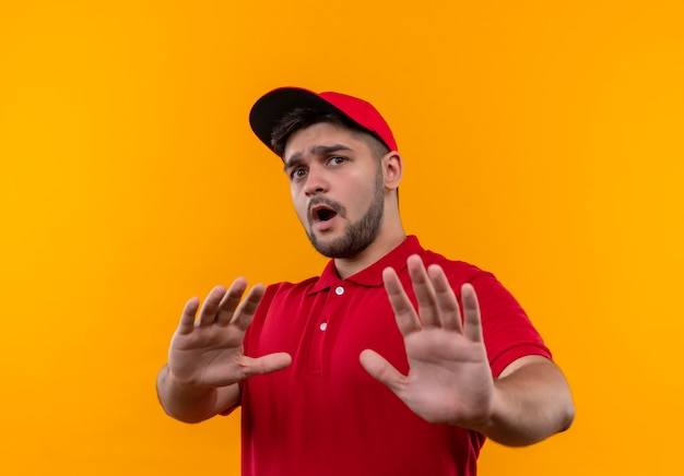 Jeune livreur en uniforme rouge et cap faisant panneau d'arrêt avec les mains inquiètes et effrayées