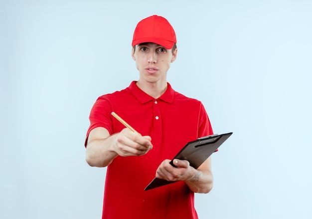 Jeune livreur en uniforme rouge et cap holding presse-papiers et crayon à l'avant avec le bras comme demandant debout sur un mur blanc