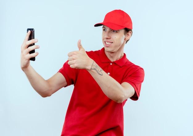 Jeune livreur en uniforme rouge et cap holding smartphone prenant selfie souriant montrant les pouces vers le haut debout sur un mur blanc