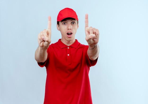 Jeune livreur en uniforme rouge et cap à la surprise montrant les index avec les deux mains debout sur un mur blanc