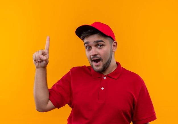 Jeune livreur en uniforme rouge et cap à la surprise de pointer avec l'index vers le haut