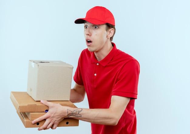 Jeune livreur en uniforme rouge et capuchon donnant des colis à un client à la surprise debout sur un mur blanc