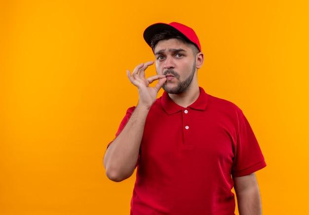 Jeune livreur en uniforme rouge et casquette faisant un geste de silence comme la fermeture de la bouche avec une fermeture éclair