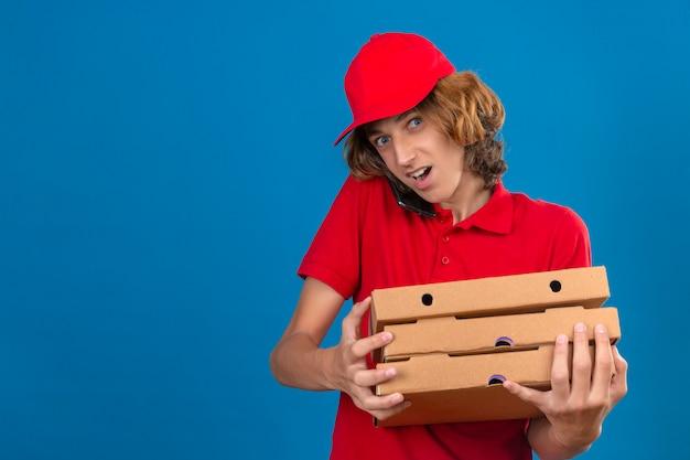 Jeune livreur en uniforme rouge tenant des boîtes de pizza tout en parlant au téléphone mobile à la surprise sur fond bleu isolé