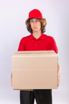 Jeune livreur en uniforme rouge tenant une grande boîte en carton regardant la caméra avec une expression triste sur le visage debout sur fond blanc isolé