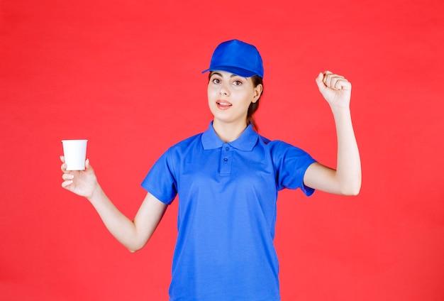 Jeune livreuse en bonnet bleu posant avec une tasse de thé en plastique sur rouge.