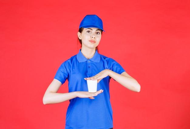 Jeune livreuse en bonnet bleu tenant une tasse de thé en plastique sur rouge.