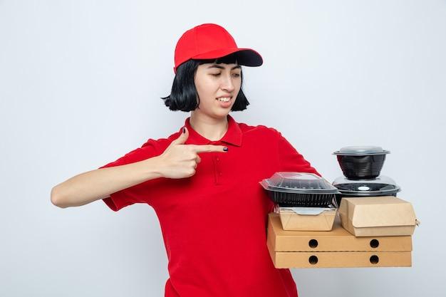 Jeune livreuse caucasienne mécontente tenant et pointant des récipients alimentaires et des emballages sur des boîtes à pizza