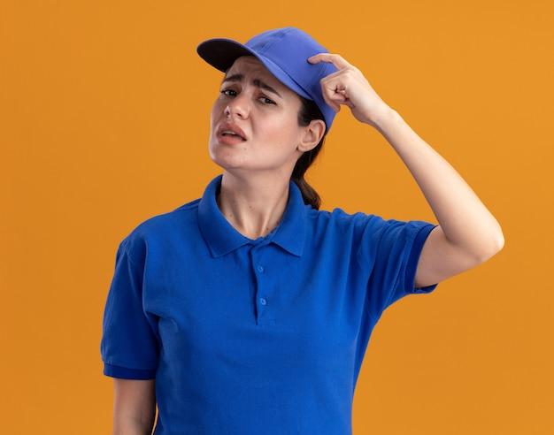 Jeune livreuse confuse en uniforme et casquette regardant la tête touchante à l'avant isolée sur un mur orange