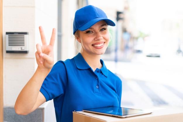Jeune livreuse à l'extérieur tenant des boîtes et une tablette et faisant un geste de victoire