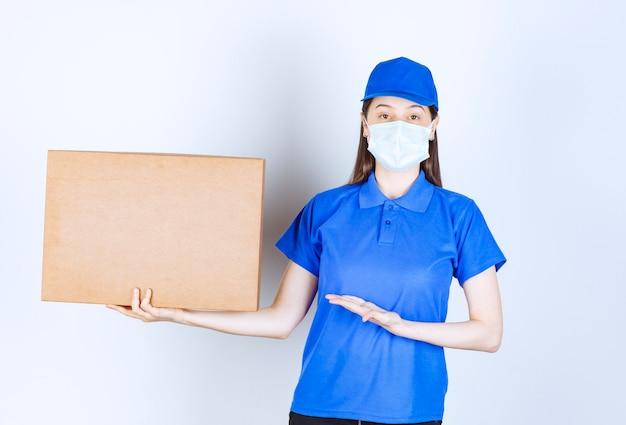 Jeune livreuse en masque médical tenant un emballage en carton.