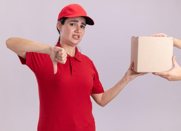Jeune livreuse mécontente en uniforme et casquette donnant une boîte à cartes au client montrant le pouce vers le bas isolé sur un mur blanc