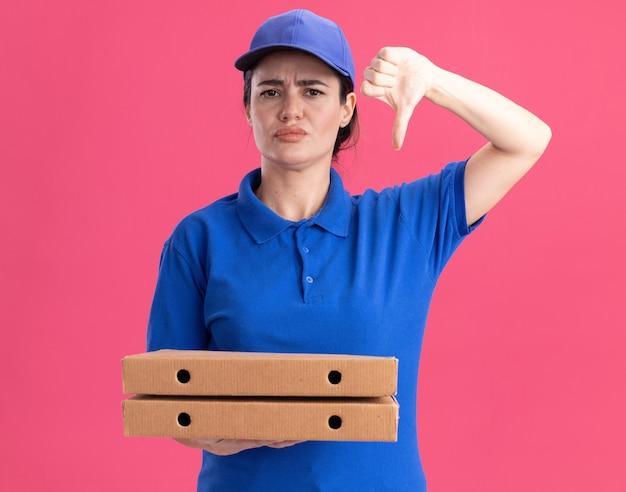 Jeune livreuse mécontente en uniforme et casquette tenant des paquets de pizza montrant le pouce vers le bas