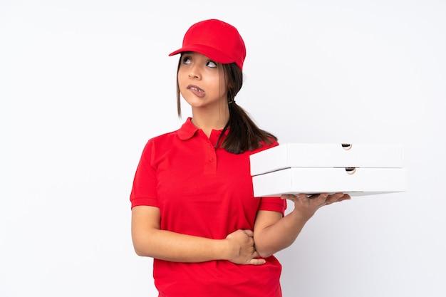 Jeune livreuse de pizza sur blanc avec l'expression du visage confus