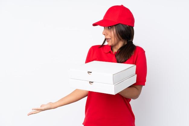 Jeune livreuse de pizza sur blanc avec une expression faciale surprise
