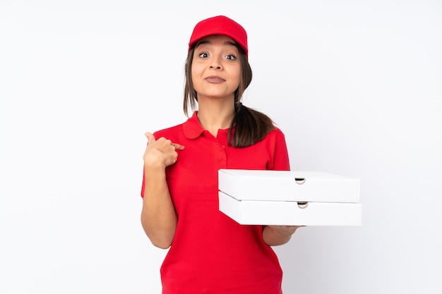 Jeune livreuse de pizza sur fond blanc isolé avec une expression faciale surprise