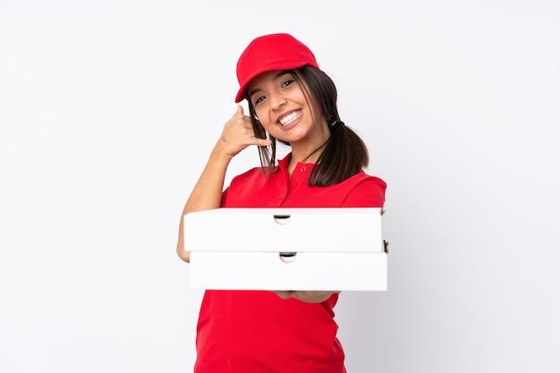 Jeune livreuse de pizza sur fond blanc isolé faisant le geste du téléphone et pointant vers l'avant