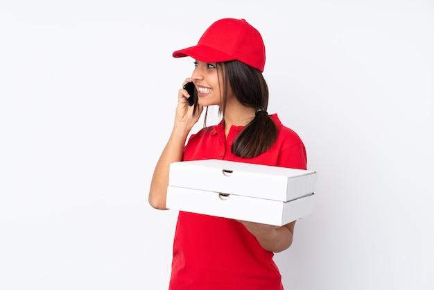 Jeune livreuse de pizza sur fond blanc isolé en gardant une conversation avec le téléphone portable avec quelqu'un