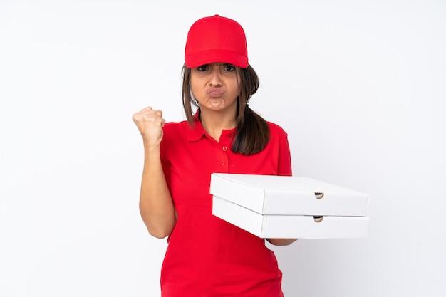 Jeune livreuse de pizza sur fond blanc isolé avec un geste de colère