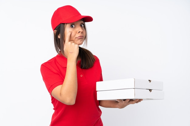 Jeune livreuse de pizza sur fond blanc isolé montrant quelque chose