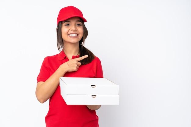 Jeune livreuse de pizza sur fond blanc isolé pointant vers le côté pour présenter un produit