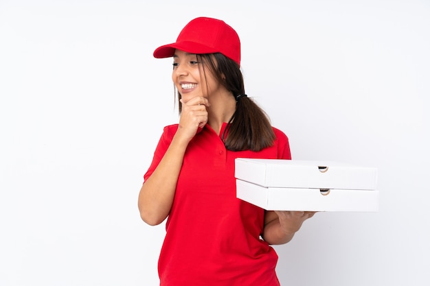 Jeune livreuse de pizza sur fond blanc isolé à la recherche sur le côté