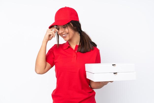 Jeune livreuse de pizza sur fond blanc isolé en riant