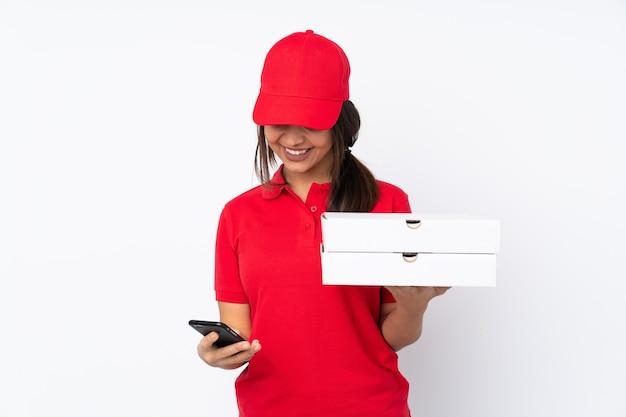Jeune livreuse de pizza sur fond blanc isolé tenant du café à emporter et un mobile