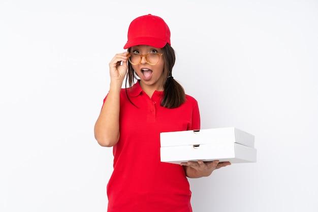 Jeune livreuse de pizza isolée avec des lunettes et surprise