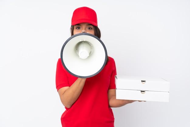 Jeune livreuse de pizza sur mur blanc isolé criant à travers un mégaphone