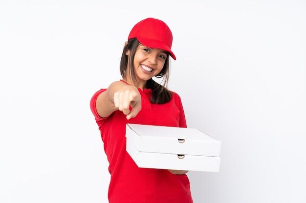 Jeune livreuse de pizza sur mur blanc isolé pointe du doigt vous avec une expression confiante