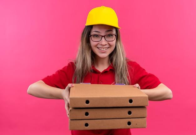 Jeune livreuse en polo rouge et casquette jaune tenant pile de boîtes de pizza regardant la caméra en souriant largement