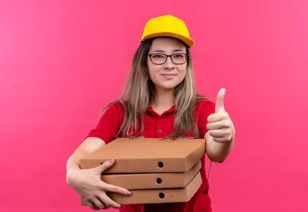 Jeune livreuse en polo rouge et casquette jaune tenant pile de boîtes de pizza regardant la caméra avec un sourire confiant sur le visage montrant les pouces vers le haut