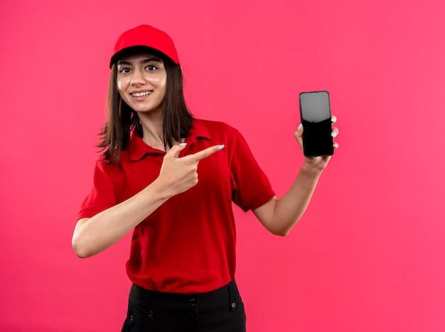 Jeune livreuse portant un polo rouge et une casquette montrant smartphone pointant avec index fionger en souriant joyeusement debout sur le mur rose