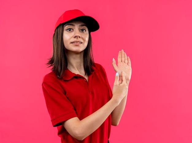 Jeune livreuse portant un polo rouge et une casquette regardant la caméra en souriant pointant son bras avec le doigt debout sur fond rose