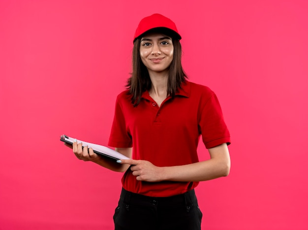 Jeune livreuse portant un polo rouge et une casquette smiling holding clipboar debout sur un mur rose