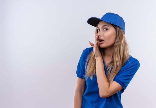 Jeune livreuse portant l'uniforme bleu et chuchotements casquette isolé sur mur blanc avec espace copie