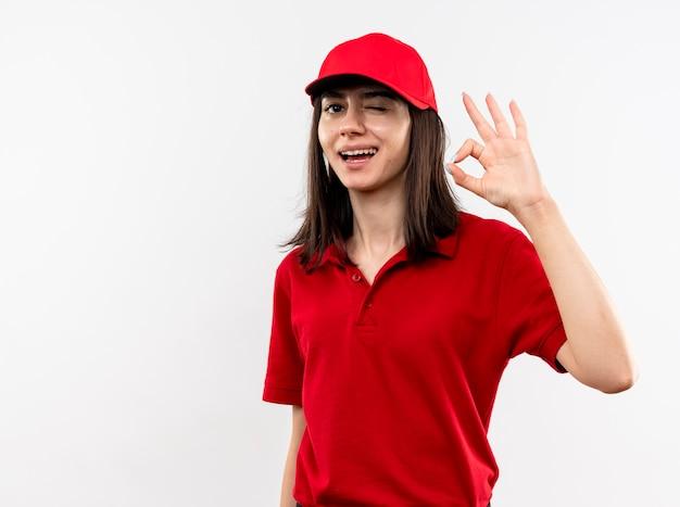 Jeune livreuse portant l'uniforme rouge et cap lookign at camera smiling with happy face clignant de l'oeil montrant signe ok debout sur fond blanc