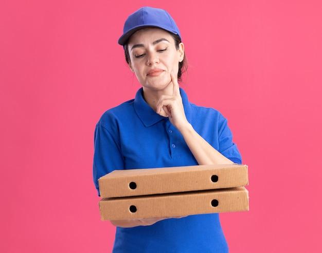 Jeune livreuse réfléchie en uniforme et casquette tenant et regardant des paquets de pizza touchant le menton isolé sur un mur rose avec espace de copie