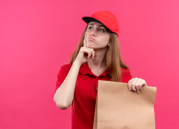 Jeune livreuse réfléchie en uniforme rouge tenant un sac en papier et mettant la main sous le menton sur un mur rose isolé avec espace de copie