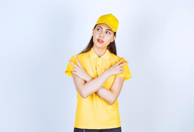 Jeune livreuse en t-shirt jaune et casquette pointant quelque part sur le blanc.