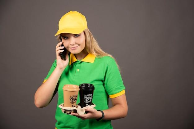 Jeune livreuse avec des tasses de café parlant sur smartphone.