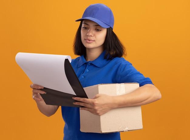 Jeune livreuse en uniforme bleu et cap holding boîte en carton et presse-papiers avec des pages vierges à la recherche de pages avec un visage sérieux debout sur un mur orange
