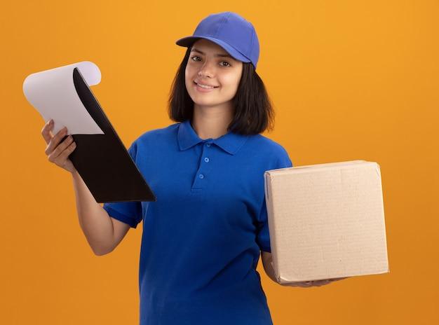 Jeune livreuse en uniforme bleu et cap holding boîte en carton et presse-papiers avec des pages vierges avec sourire sur le visage debout sur un mur orange