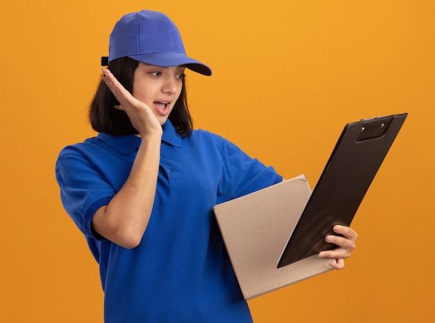 Jeune livreuse en uniforme bleu et cap holding boîte en carton et presse-papiers à la regarder surpris debout sur un mur orange