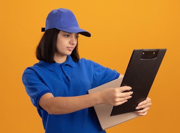 Jeune livreuse en uniforme bleu et cap holding boîte en carton et presse-papiers à la regarder avec un visage sérieux debout sur un mur orange